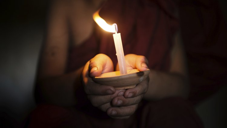 Buddhist with candle