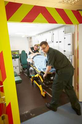 Paramedic wheeling patient on stretcher from ambulance to take to Emergency Department. The ambulance simulator's authentic surroundings and latest patient medical simulators provide a realistic and authentic environment for student nurses to train in