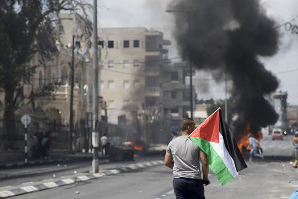 A protestor waves a Palestinian flag in front of burning barricades during a protest against Israel's ongoing occupation of Palestine
