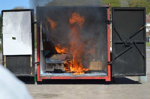 Hot unburnt combustion products (smoke) from the burning of materials starts to rise and accumulate at ceiling level while flame impingement causes the fire to spread further throughout the room.