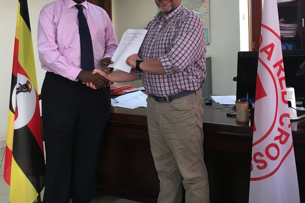 The Secretary General of the Ugandan Red Cross, Robert Kewsiga (left) signs the MOU with Jeff Evans, course leader for the MSc Disaster Healthcare