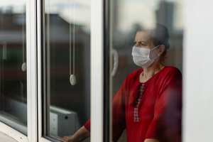 Lady wearing facemask in window